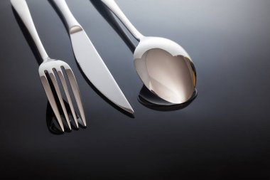 silver knife and fork, spoon, on a black background.