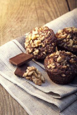 Homemade delicious chocolate Muffins with Walnut on wood backrou