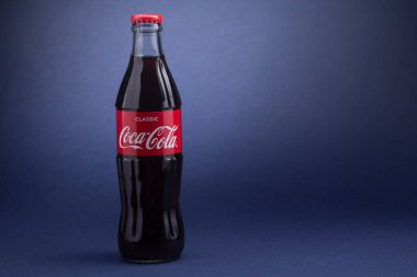 Belgorod , Russia - MAY, 28, 2020: Classic Coca-Cola bottle on Blue Background. Carbonated soft drink produced by Coca-Cola.