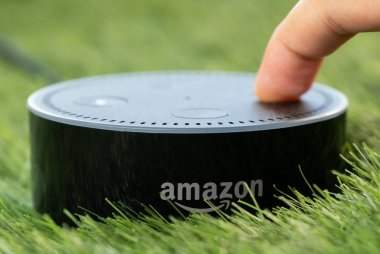 TOKYO, JAPAN - JULY 8TH, 2018. Amazon's Echo Dot, Alexa virtual assistant on green grass.