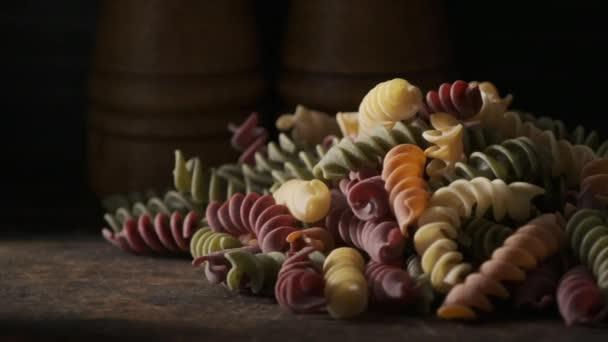 Dried colored fusilli pasta on wooden board
