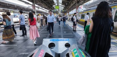 TOKYO, JAPAN - JULY 16TH, 2018. Commuters  in Japan Railway train during the morning rush hour in Shinjuku Station.
