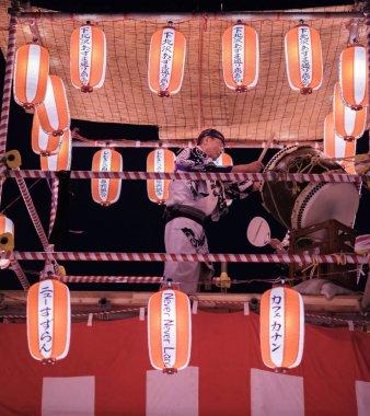 TOKYO, JAPAN - AUGUST 12TH, 2018. Taiko drummer pounding drum at the Bon Odori celebration in Shimokitazawa neighborhood at night.