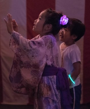 TOKYO, JAPAN - AUGUST 12TH, 2018. Little Japanese girl dancing at the Bon Odori celebration in Shimokitazawa neighborhood at night.