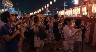 TOKYO, JAPAN - AUGUST 12TH, 2018. Crowd of people dancing at the Bon Odori celebration in Shimokitazawa neighborhood at night.