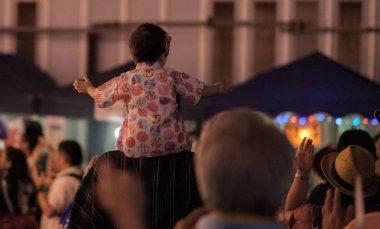 TOKYO, JAPAN - AUGUST 12TH, 2018. Little girl on his father's shoulder dancing at the Bon Odori celebration in Shimokitazawa neighborhood at night.