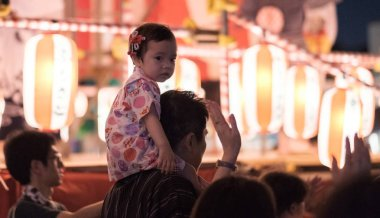 TOKYO, JAPAN - AUGUST 12TH, 2018. Little girl on his father's shoulder dancing at the Bon Odori celebration in Shimokitazawa neighborhood at night.