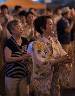 TOKYO, JAPAN - AUGUST 12TH, 2018. Dancers in traditional yukata dancing at the Bon Odori celebration in Shimokitazawa neighborhood at night.