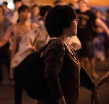 TOKYO, JAPAN - AUGUST 12TH, 2018. Woman dancing at the Bon Odori celebration in Shimokitazawa neighborhood at night.