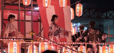 TOKYO, JAPAN - AUGUST 12TH, 2018. Dancers in traditional yukata dancing on the stage at the Bon Odori celebration in Shimokitazawa neighborhood at night.