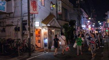 TOKYO, JAPAN - AUGUST 12TH, 2018. People walking in the backstreet of Shimokitazawa neighborhood street at night.