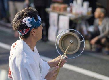 TOKYO, JAPAN - AUGUST 19TH, 2018.  Musician playing traditional kane bell accompanying dance troupe in the street during Awa Odori festival in Shimokitazawa.