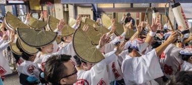 TOKYO, JAPAN - AUGUST 19TH, 2018. Female dancers wearing amigasa straw hat and kimono performing in the street during Awa Odori festival in Shimokitazawa.