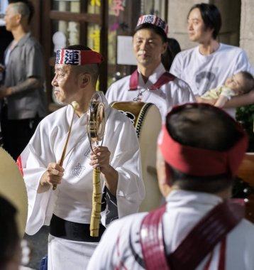 TOKYO, JAPAN - AUGUST 19TH, 2018.  Musician playing traditional kane bell accompanying dance troupe in the street during Awa Odori festival in Shimokitazawa.