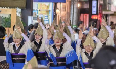 TOKYO, JAPAN - AUGUST 19TH, 2018. Female dancers wearing amigasa straw hat and kimono performing in the street during Awa Odori festival in Shimokitazawa.