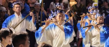 TOKYO, JAPAN - AUGUST 19TH, 2018.  Musician playing traditional shinobue flute accompanying dance troupe in the street during Awa Odori festival in Shimokitazawa.