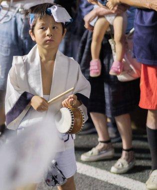 TOKYO, JAPAN - AUGUST 19TH, 2018.  Japanese boy musician playing traditional taiko drums accompanying dance troupe in the street during Awa Odori festival in Shimokitazawa.