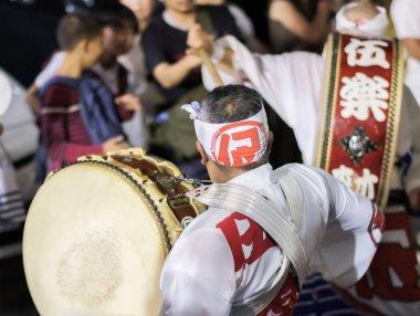 TOKYO, JAPAN - AUGUST 19TH, 2018.  Musician playing traditional taiko drums accompanying dance troupe in the street during Awa Odori festival in Shimokitazawa.