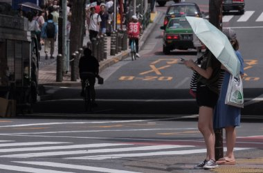 TOKYO, JAPAN - AUGUST 19TH, 2018. Japanese girl with smartphone holding an umbrella waiting to cross the street in Shibuya.