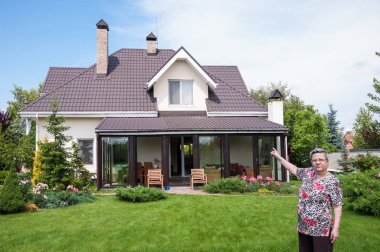 A lovely old woman showing a private house