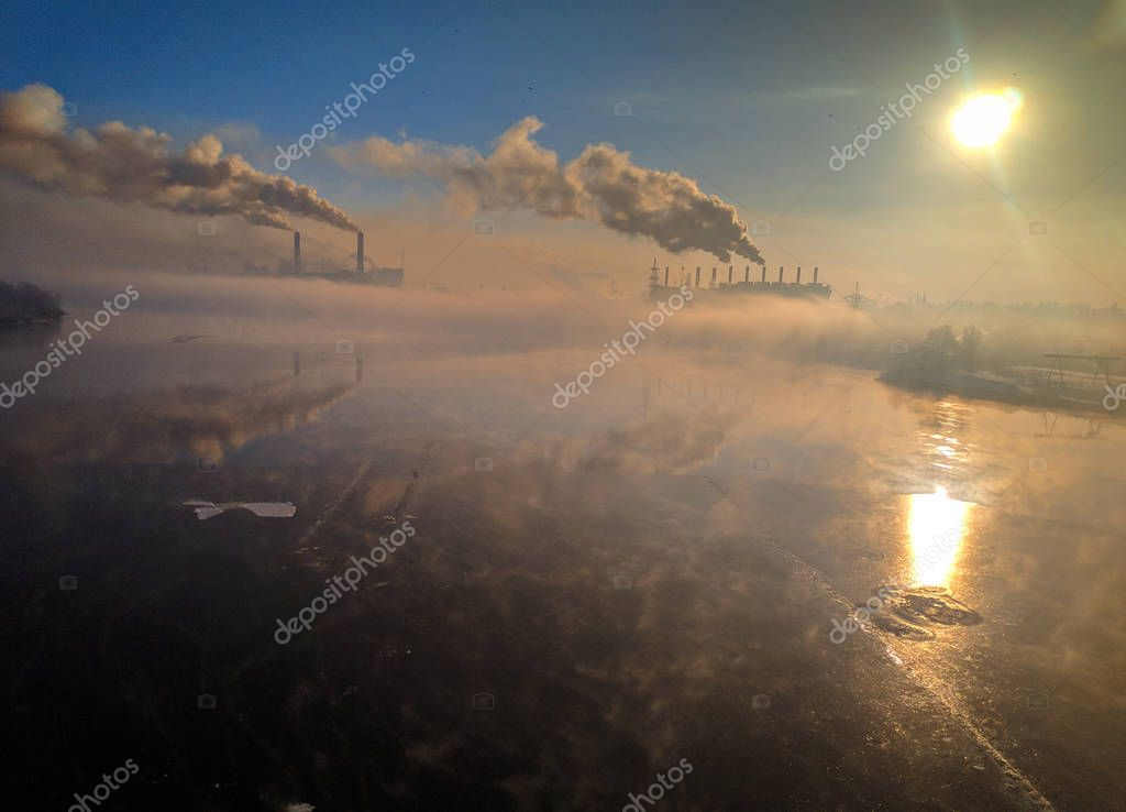 winter landscape river with ice, smoke from the pipes of the plant, river port in winter