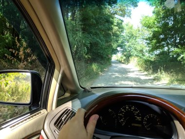 riding inside a car. vehicle interior. driver rides on a dirt road.