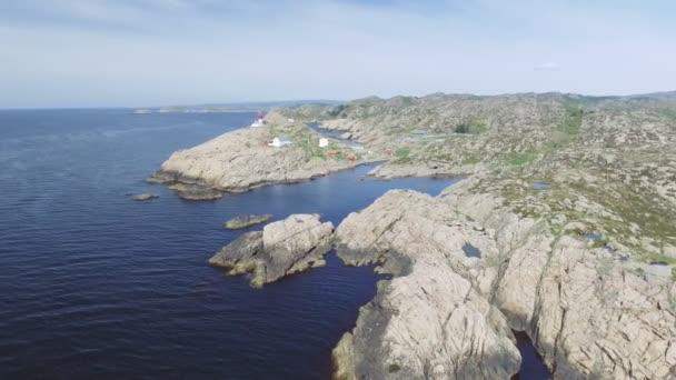Video z majáku Lindesnes v létě, Jižní Norsko. Letecký snímek. Kamenné moře pobřeží a modrá obloha