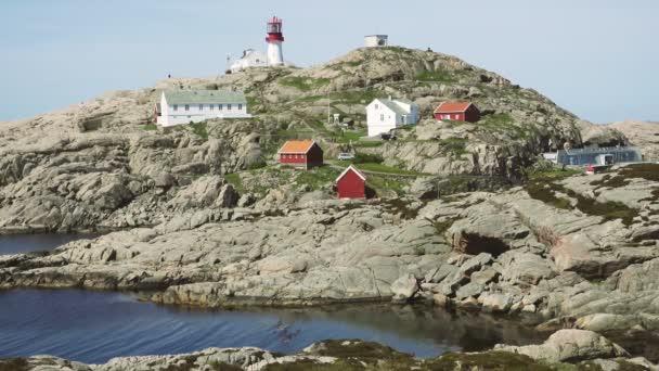 Video z majáku Lindesnes v létě, Jižní Norsko. Letecký snímek. Kamenné moře pobřeží a modrá obloha.