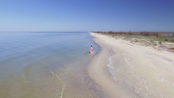 Aerial view of beautiful woman alone in an amazing and unspoiled beach in the sea coast
