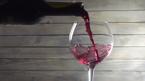 Rotwein vor hölzernem Hintergrund ins Glas gießen. Zeitlupe