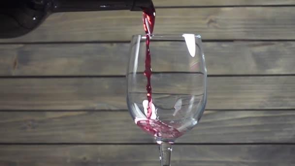 Vörösbort öntök a pohárba a fa háttér ellenére. Lassú mozgás.