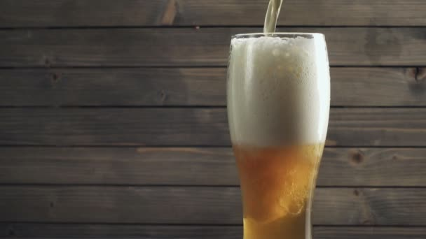 Beer poured in glass on wood background. Slow motion