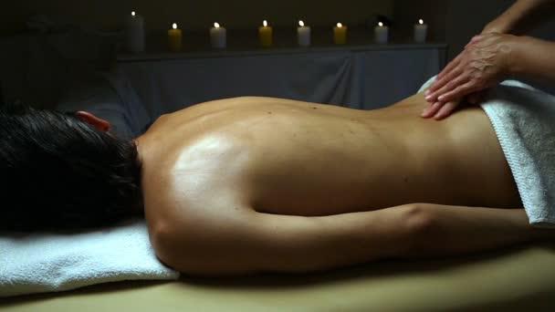 Aufnahme einer professionellen Masseurin, die Rücken und Schultern eines männlichen Kunden massiert.