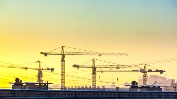 silhouette of cranes working on construction site on sunset sky background.