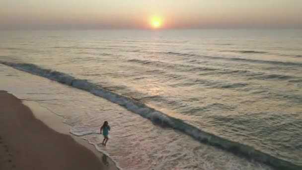 štíhlá sportovní žena je na pobřeží sama, brzy ráno. Východ slunce