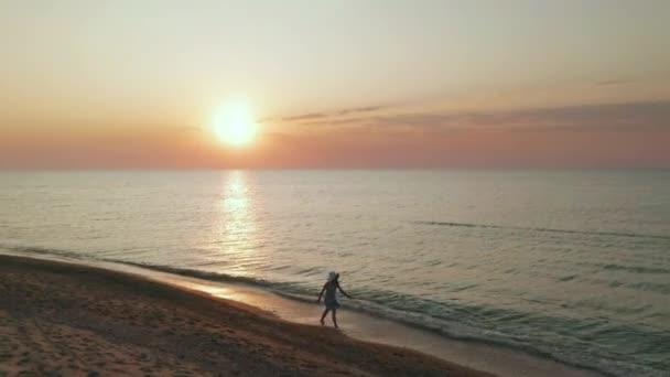 Krásná scéna ženy, která se při západu slunce prochází po pláži. Radostná šťastná dívka relaxující s radostí a štěstím v útlým těle pro dietní dietu. Letecký pohled.