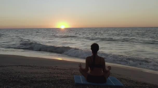 Gyönyörű fiatal nő ül jóga a strandon, miközben nézi a naplementét.