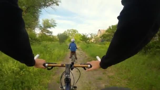 Chlapec jezdí na kole na pěšině v lese. Cesta v jarním parku.