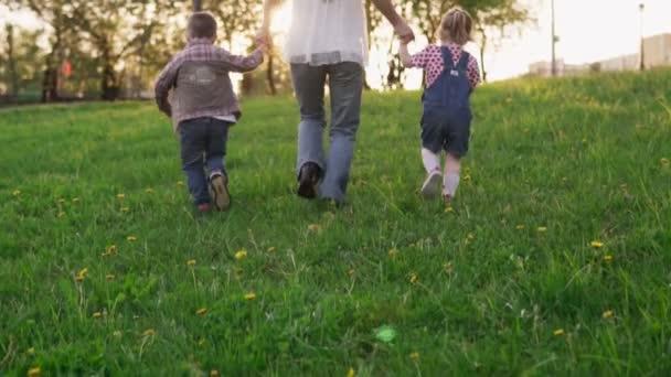 Matka a malé děti, drželi se za ruce a běží v parku při západu slunce