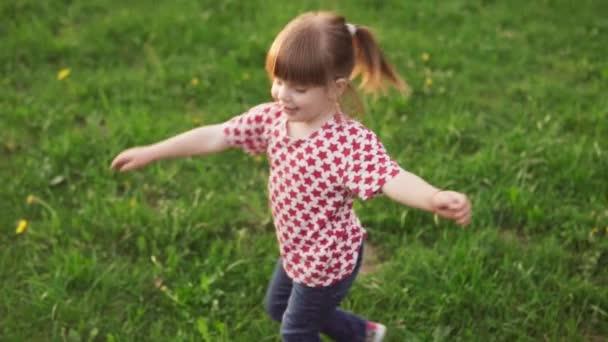 Bezstarostné holčička tančí na trávě v parku