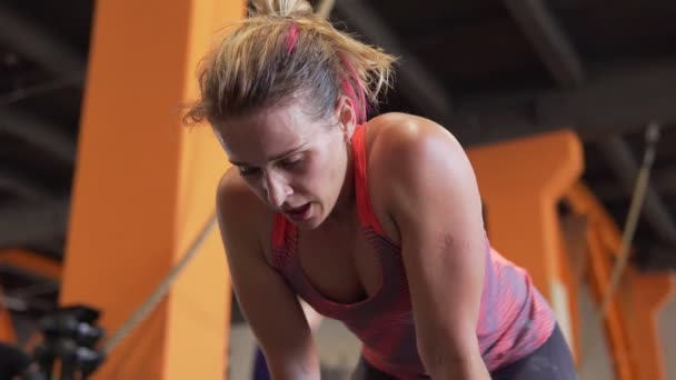 Tired fitness woman leans over and breathing heavily after exercise in gym