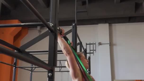 Fitness žena dělá bar muscle-up cvičení v tělocvičně