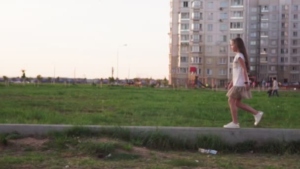 Cute little girl walking on concrete log on city lawn