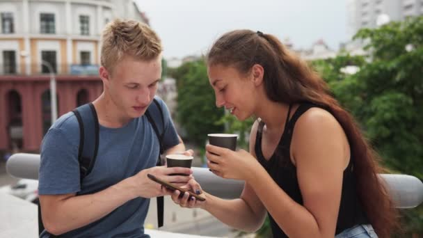 Two young people talking, drinking coffee and using smartphone at urban street