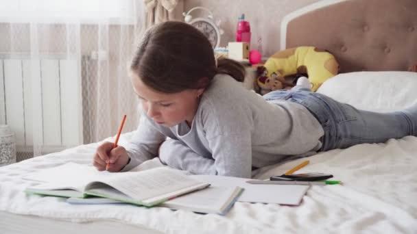 Kleines Mädchen schaut in Buch und schreibt in Notizbuch auf dem Bett zu Hause