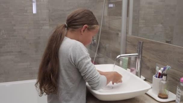 Malá holka myje ruce pod tekoucí vodou v koupelně
