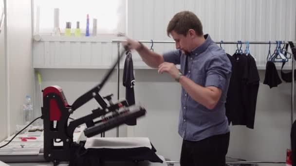 d0eb5eb836cb Ιδιοκτήτης μικρής επιχείρησης ο άνθρωπος χρησιμοποιεί χέρι πιέστε για  εκτύπωση σε ρούχα στο εργαστήριο– πλάνα αρχείου