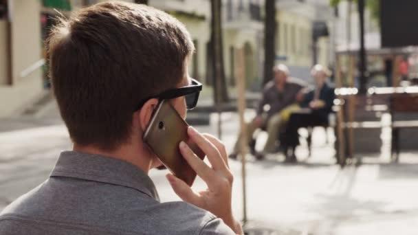 Evropská obchodní muž mluví na mobilním telefonu na slunečný den na městské ulici