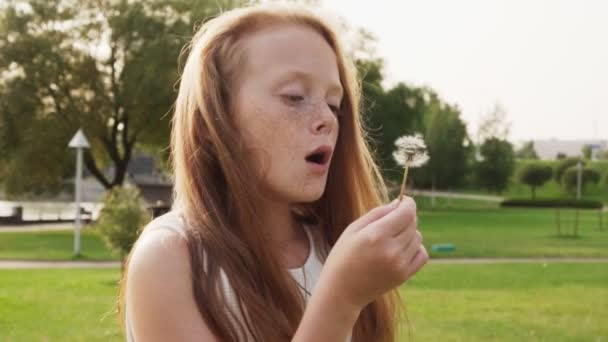 Beautiful red-haired little girl with freckles blowing on dandelion in park