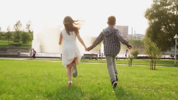 Carefree children holding hands and running together on grass in summer park